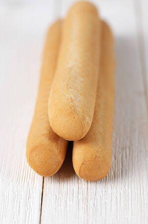 breadsticks: Breadsticks on white wooden background. Foto de archivo