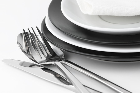 cubiertos de plata: Configuración de la tabla: placas en blanco y negro y cubiertos establecidos en el fondo blanco.