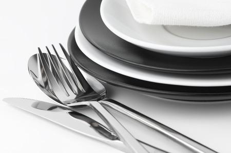 Tabelleneinstellung: Schwarz-Weiß-Teller und Besteck auf weißen Hintergrund.