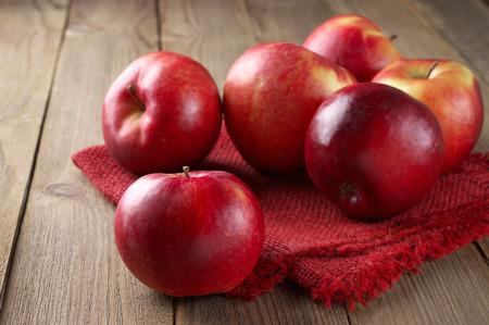 リネン ナプキン素朴な木製のテーブルの上に赤いリンゴ。 写真素材