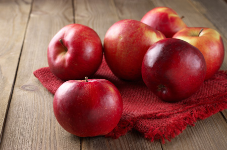 Red apples with linen napkin on rustic wooden table.