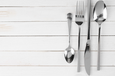 Cutlery set knife fork and spoons on white wooden background. photo & Cutlery Set: Vintage Knife Fork And Spoon On White Wooden ...