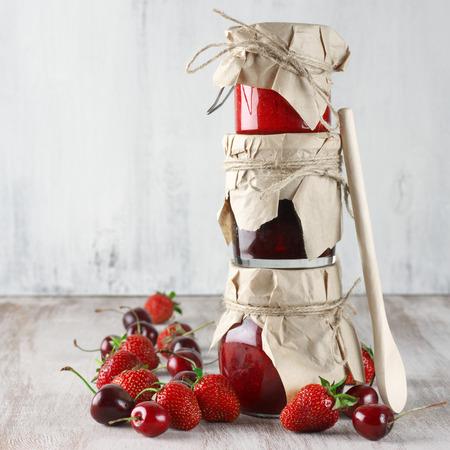 mermelada: Pila de mermeladas en frascos de vidrio con cuchara de madera y bayas frescas en el fondo de madera rústica.