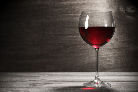 table glass: Glass of red wine on rustic wooden background with copy space.
