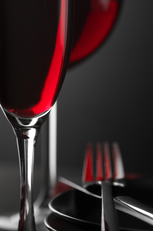 restaurant tables: Close-up of two glass of red wine, plates and silverware on dark wooden table. Shallow DOF. Stock Photo