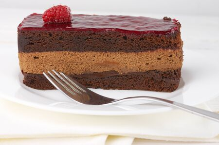 raspberry jelly: Slice of chocolate layered cake with souffle, fruity jelly and raspberry on white plate. Stock Photo