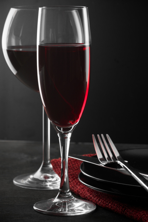 restaurant tables: Two glass of red wine, plates and silverware on dark wooden table.