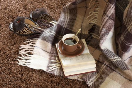 shaggy: Woolen plaid, coffee cup, book and slippers on shaggy carpet. Top view.