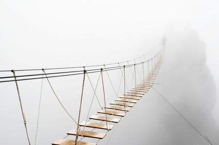 aventura: Borrosa hombre caminando sobre puente colgante de desaparecer en la niebla. Foto de archivo