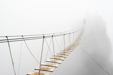 dangerous: Fuzzy man walking on hanging bridge vanishing in fog. Stock Photo