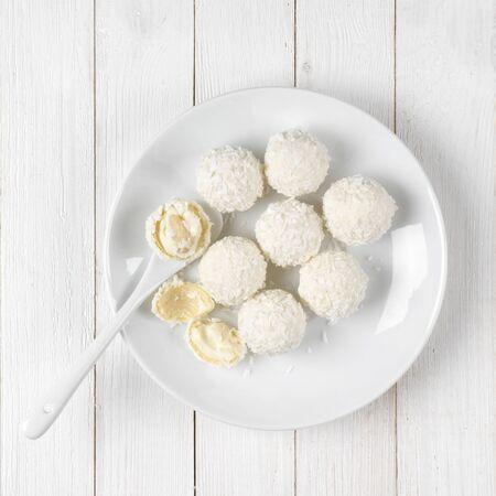 cocotier: Toute blanche et brisés boules de noix de coco bonbons plaque sur fond blanc en bois rustique. Top point de vue. Banque d'images