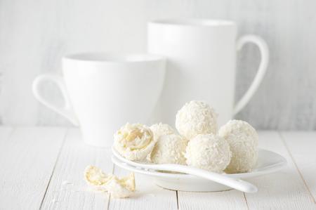 cafe bombon: Toda blanca y bolas de caramelo de coco roto en plato, taza y taza en fondo de madera r�stica. Estilo de comida Blanca. Foto de archivo