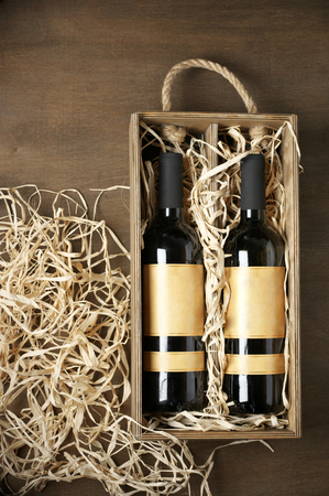 vintage bottle: Two closed wine bottles lying on straw in vintage wooden box on wood background. Top view point.