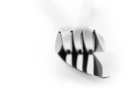 tine: Close-up of fork and knife isolated on white background. Soft focus, shallow DOF. Focus on top of prongs.