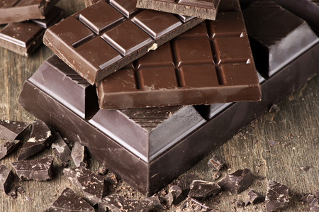 chocolate bar: Assorted dark chocolate bars and chopped chocolate on vintage wooden background.