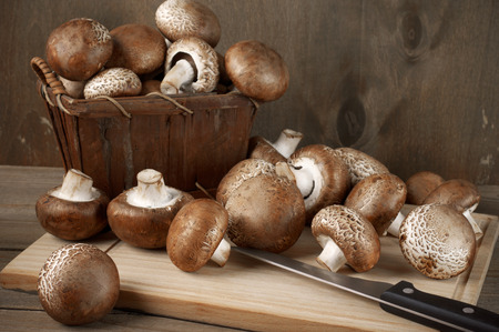 bast basket: Brown cap mushrooms in bast basket and on cutting board with knife on rustic wooden background.
