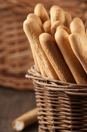 gressins: Breadsticks in basket on wooden background. Banque d'images