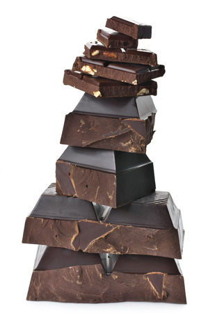 Stack of assorted broken dark chocolate pieces isolated on white background. Stockfoto