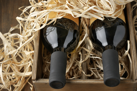 haulm: Two closed wine bottles lying on straw in vintage wooden box close-up.