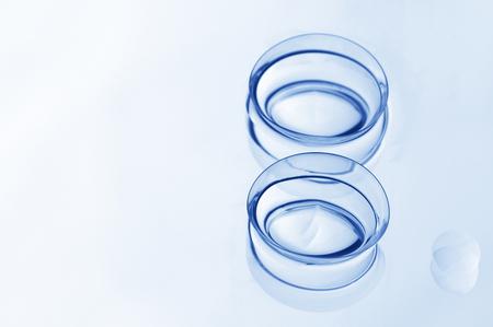 lentes de contacto: Dos lentes de contacto blandas húmedas con la reflexión close-up sobre fondo claro con espacio de copia. DOF bajo. Entonado imagen. Foto de archivo