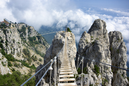 Hanging bridge in steep rocks with going man. Ai-Petri, Crimea. Standard-Bild