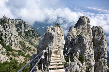 Hanging bridge in steep rocks with going man. Ai-Petri, Crimea. Stockfoto