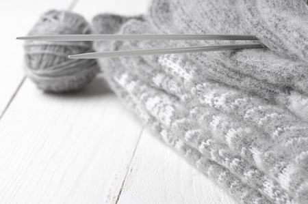 weave ball: Stack of gray warm fluffy knitwear with knit needles and ball on white wood. Soft focus, shallow DOF.