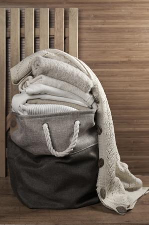 knitwear: Stack of warm white knitwear in fabric basket in wooden bathroom. Stock Photo