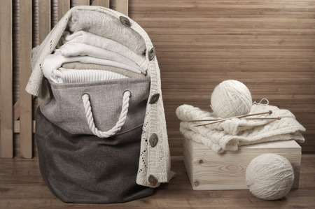 weave ball: Stack of warm white knitwear in fabric basket in wooden bathroom. Stock Photo