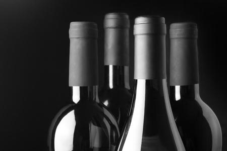 tomando vino: Cuatro botellas de vino variedad de close-up sobre fondo negro. Monocrom�tico blanco y negro de la imagen. Centran en la botella delante. Foto de archivo
