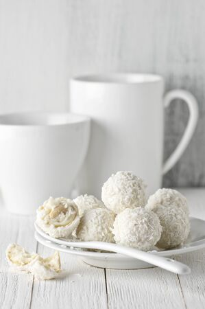 rustic food: White whole and broken coconut candy balls in plate, cup and mug on rustic wooden background. White food styling. Stock Photo