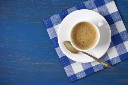 napkin: White cup of coffee with checkered napkin on blue wooden table. Top view point.