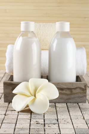 shower gel: Set of bathroom accessory on stone tile: frangipani-shaped soap, shower gel, lotion, towel, loofah.