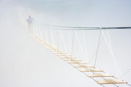 ambiguity: Man walking on hanging bridge in fog. Stock Photo