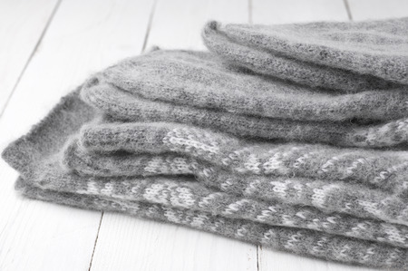 tricot: Stack of gray warm fluffy knitwear on white wood. Stock Photo