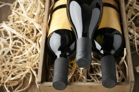 box: Three closed wine bottles lying on straw in vintage wooden box.