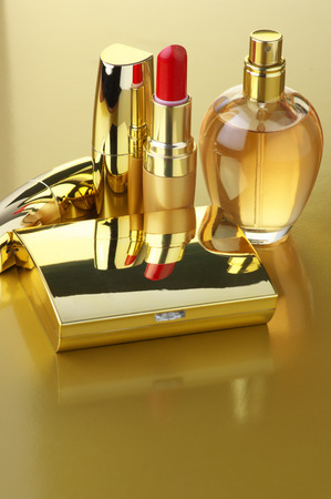 of cosmetics: Cosmetic set. Gold powder, lipsticks and perfume on golden background. Stock Photo