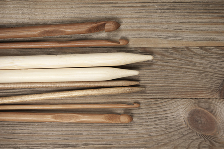 space needle: Various wooden knitting needles and crochets set on rustic wooden background. Top view point.