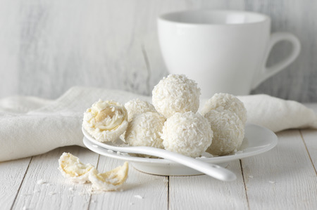 White whole and broken coconut candy balls in plate and cup on rustic wooden background. White food styling. Archivio Fotografico