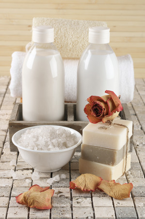 gel douche: Set of bathroom accessory on stone tile: soaps stack with dried rose, bath salt,  shower gel, lotion, towel, loofah.