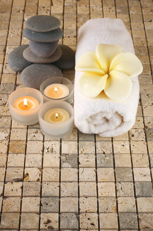 the candle: SPA still life on stone tile in warm light: candles, frangipani-shaped soap on towel and stack of stones. Archivio Fotografico