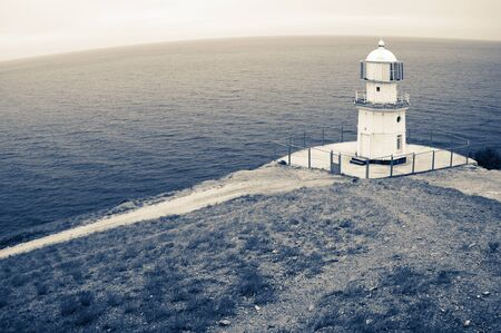 lighthouse: Old lighthouse on top of rock against sea with round horizon. Fisheye view, filtered toned image.