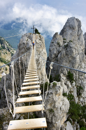 dangerous: Hanging bridge in steep rocks with going man. Ai-Petri, Crimea. Stock Photo