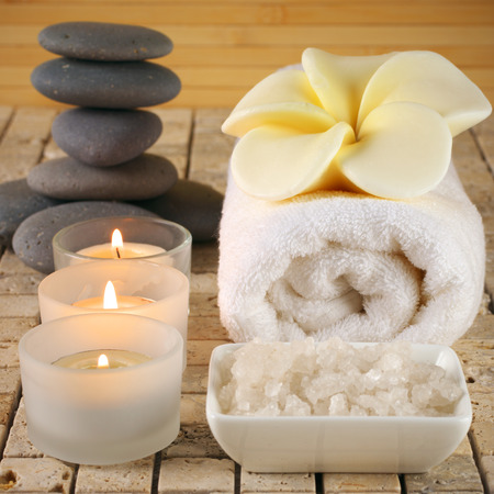 set in stone: SPA still life on stone tile in warm light: candles, frangipani-shaped soap on towel and stack of stones. Stock Photo
