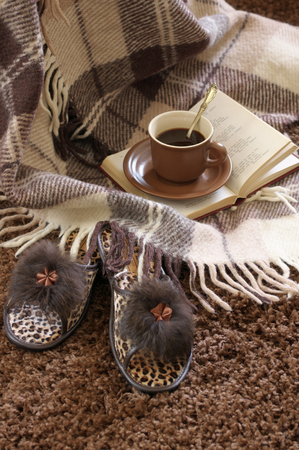 shaggy: Woolen plaid, coffee cup, book and slippers on shaggy carpet. Stock Photo