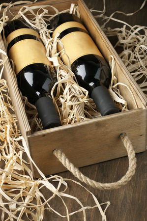 wooden box: Two closed wine bottles lying on straw in vintage wooden box.