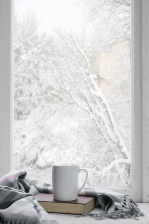 居心地の良い冬の静物: 熱いお茶と外から雪の風景を窓辺に温かみのあるチェック柄のついた本のマグカップ。 写真素材