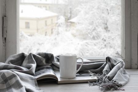 Acogedor invierno todavía la vida: taza de té caliente y libro abierto con tela escocesa caliente sobre alféizar de la vendimia contra el paisaje de nieve desde fuera. Foto de archivo