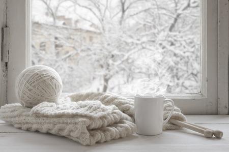 gomitoli di lana: Accogliente inverno ancora vita: tazza di tè caldo e caldo di lavoro a maglia di lana sul davanzale d'epoca contro la neve paesaggio dall'esterno.