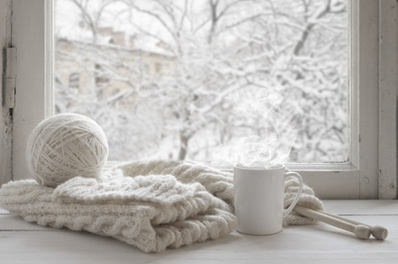 Cozy winter still life: mug of hot tea and warm woolen knitting on vintage windowsill against snow landscape from outside. Standard-Bild